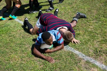 芝生のフィールドでラグビーを再生しながらボールを追う男のハイアングル 写真素材