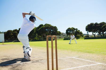 晴れた空に対してフィールドでクリケットを再生しながらバッティング プレーヤーの背面図