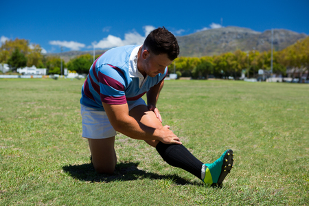 Young rugby player stretching on grassy field on sunny day Stock Photo