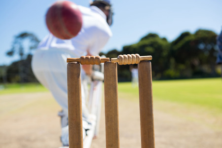 Close up of ball by stump against batsman on field Stock Photo