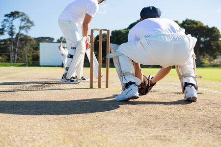 Rear view of wicket keeper crouching by stumps during match on sunny day Stock Photo