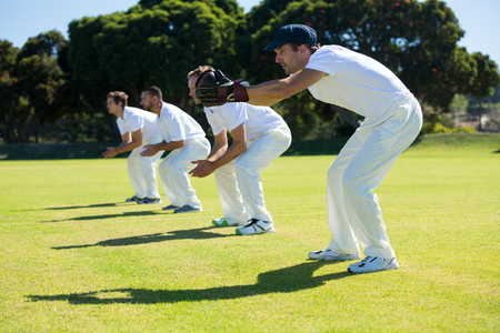 Side view of fielders bending while standing at field on sunny day