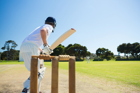 Side view of cricket player batting while playing on field against clear sky