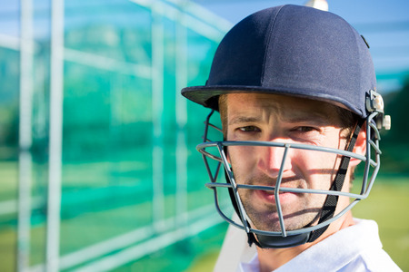Portrait of cricket player wearing helmet standing at pitch
