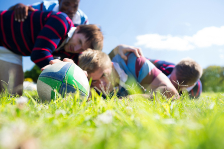 Close up of men playing rugby while lying at grassy field on sunny day