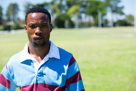 Portrait of serious rugby player standing at field on sunny day Stock Photo