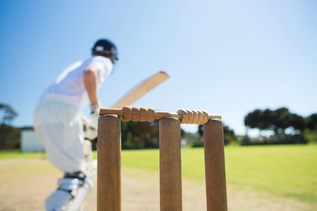 Close up of wooden stump by batsman standing on field against clear sky Stock Photo