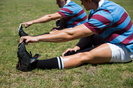 Close up of rugby players stretching while sitting on grassy field Stock Photo