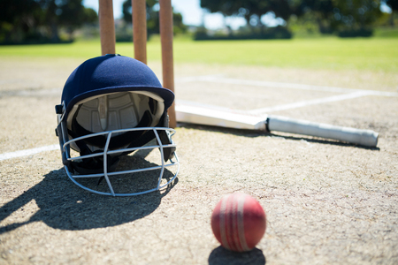 Sports helmet and ball with bat by stumps on pitch during sunny day
