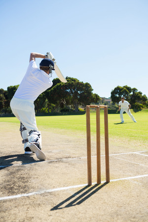 Rear view of cricket player batting while playing on field against clear sky