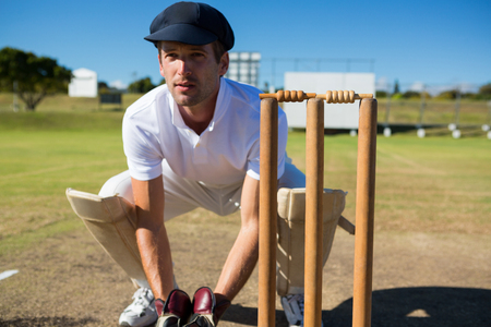 Wicket keeper crouching by stumps during match on sunny day