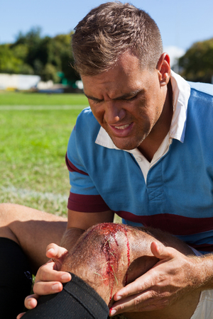Rugby player with injured knee sitting on field