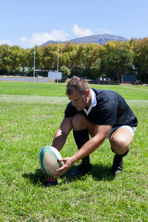 Full length of player kneeling while holding rugby ball on grassy field Stock Photo