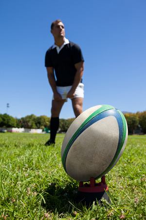Close-up of rugby ball on grassy field with player standing in background