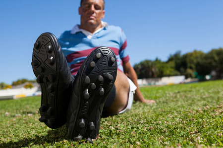 Full length of rugby player sitting on field during sunny day Stock Photo
