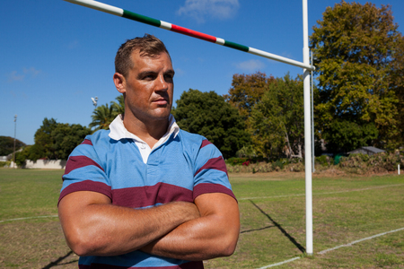 Thoughtful rugby player with arms crossed standing at playing field on sunny day