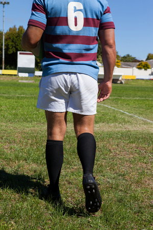 Rear view of rugby player walking on field during sunny day