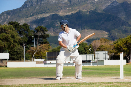 Batsman playing cricket on field against mountain during sunny day Stock Photo