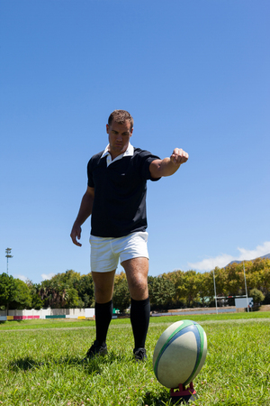 Full length of rugby player kicking ball on grassy field against clear blue sky