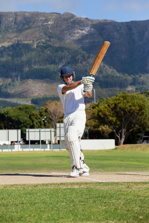 Full length of batsman playing cricket on field during sunny day Stock Photo