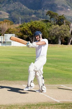 Batsman playing cricket at field on sunny day Stock Photo