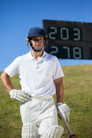 Confident cricket player with bat standing against scoreboard at field