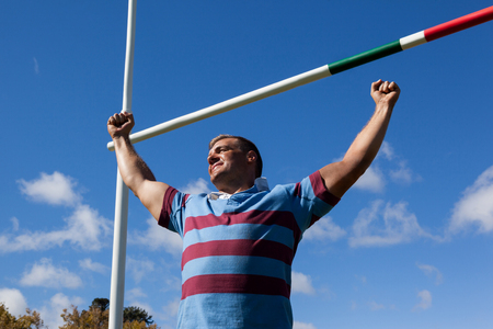 Low angle view of smiling rugby player with arms raised by goal post against blue sky Stock Photo