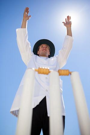 Low angle view of cricket umpire signalling six at match during sunny day