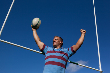 Low angle view of happy rugby player holding ball with arms raised by goal post against blue sky Stock Photo