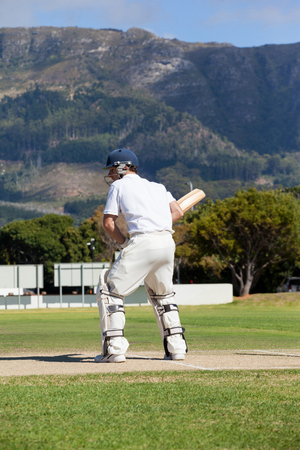 Rear view of batsman playing cricket at field on sunny day