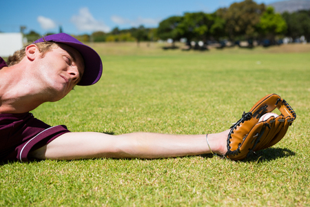 Baseball pitcher catching ball while diving on field during sunny day Stock Photo