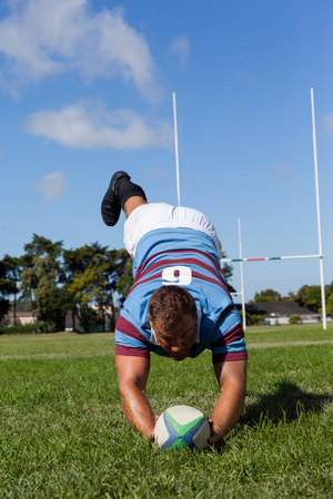 post man: Full length of player playing rugby on field during sunny day against blue sky