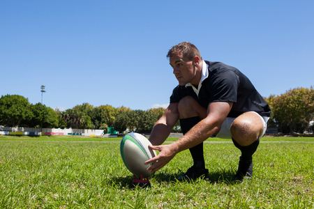 Rugby player holding ball while kneeling on grassy field against clear sky Stock Photo