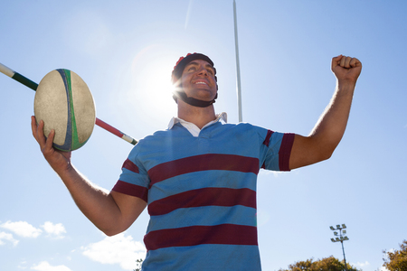 Low angle view of happy player holding rugby ball with arms raised by goal post against blue sky Stock Photo