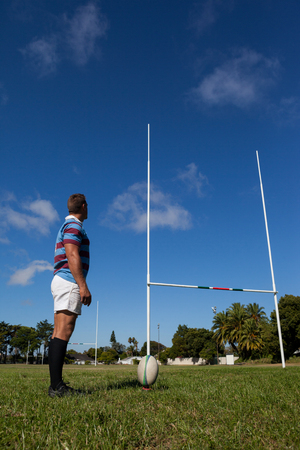 Side view of rugby player looking at goal post against blue sky on field Stock Photo
