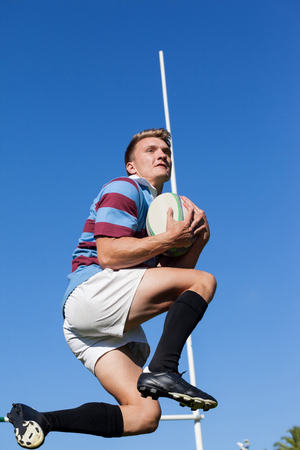 Low angle view of rugby player catching ball against clear blue sky Stock Photo