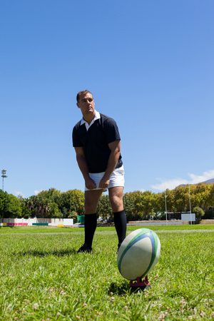 Rugby player looking away while standing by ball on grassy field against clear blue sky Stock Photo