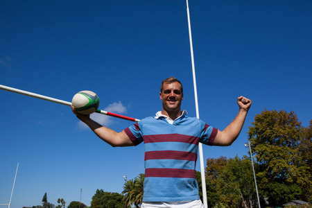 Portrait of happy rugby player holding ball with arms raised by goal post against blue sky