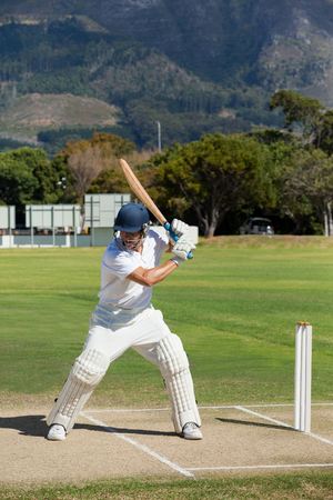 Cricket player practicing on field during sunny day Stock Photo
