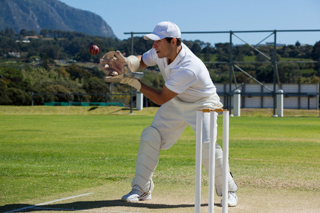 Full length of wicketkeeper catching cricket ball behind stumps on field during sunny day Stock Photo