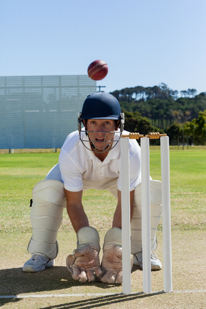 Wicketkeeper looking at ball crouching behind stumps on field against clear blue sky