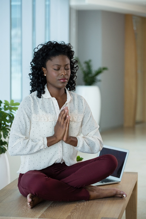 Female executive meditating on desk in office Stock Photo