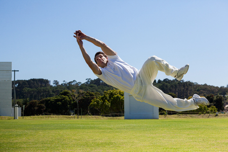 Full length of player diving to catch ball against blue sky over field Stock Photo