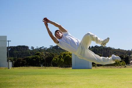 Longitud total del jugador de buceo para atrapar la pelota contra el cielo azul sobre el campo Foto de archivo - 79189263