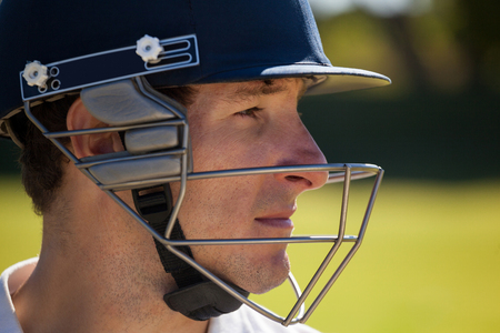 Close up of cricketer wearing helmet while playing at field
