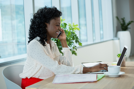 Female executive using laptop at desk in office Stock Photo
