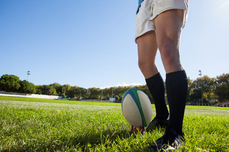 Low section of player standing by rugby ball on playing field against clear blue sky