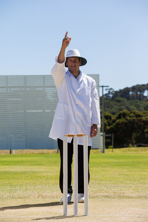 Cricket umpire signalling out during match on sunny day against clear sky