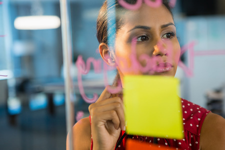 Thoughtful female executive looking at sticky notes in office Stock Photo