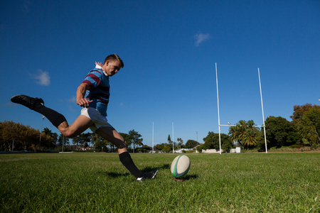 Full length of rugby player kicking ball for goal against clear blue sky